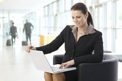 Businesswoman working on laptop at lobby stock image