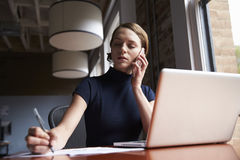 Businesswoman Working On Laptop And Making Phone Call Stock Images