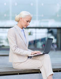 Businesswoman working with laptop outdoors stock photos