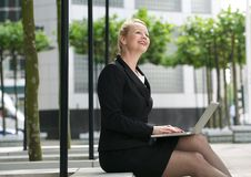 Businesswoman working on laptop outdoors Royalty Free Stock Image