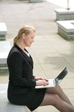 Businesswoman working on laptop outside the office Royalty Free Stock Image