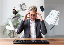 Businesswoman working on a laptop, overworking, under pressure. And stress, objects flying around her Stock Photo