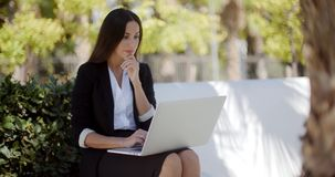 Businesswoman working on a laptop in a park stock video