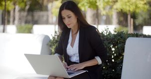 Businesswoman working on a laptop in a park stock video footage