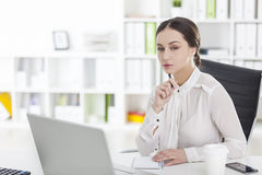 Businesswoman working on laptop with pen, side Stock Photos
