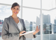 Businesswoman working on laptop and smiling at camera Stock Image