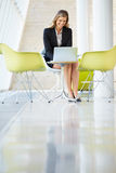 Businesswoman Working On Laptop At Table In Modern Office Stock Photography