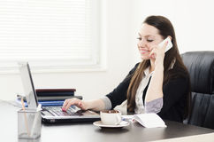 Businesswoman is working on laptop and using smart phone Royalty Free Stock Images