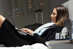 Businesswoman working late hours during business travel. Lying on the bed of an hotel room royalty free stock image