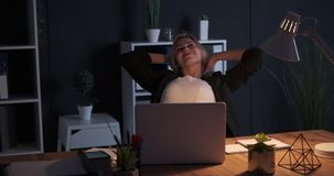 Businesswoman working late night and stretching at office. Tired businesswoman working and stretching at night office stock video footage