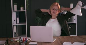 Businesswoman working late and stretching at office. Tired businesswoman working overtime and stretching at office stock footage