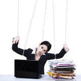 Businesswoman working like marionette. Portrait of businesswoman working while controlled by using strings. isolated on white background stock image