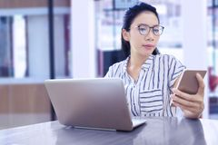 Businesswoman working with mobile phone and laptop royalty free stock images