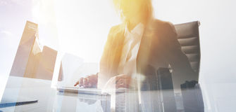 Businesswoman working at modern office on desktop computer.Young woman working process.Double exposure,skyscraper. Building blurred background.Horizontal.Flares royalty free stock photo