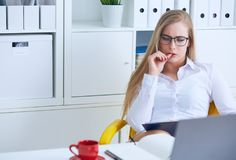 Young beauiful Caucasian businesswoman in glasses intently working on notebook computer and business document at office. royalty free stock image