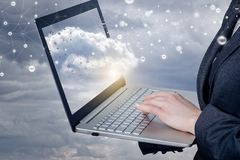 A businesswoman working with notebook with network connections cloud on it screen royalty free stock image