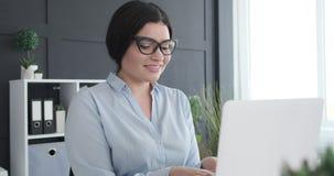 Businesswoman working on office laptop. Happy businesswoman working on laptop at office stock video