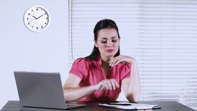 Bored businesswoman working at workplace. Businesswoman working in the office and looks bored, writing on a paperwork with laptop on desk stock footage