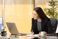 Businesswoman working online and taking notes stock image