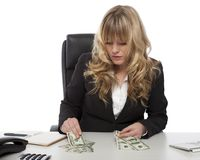 Businesswoman working out her finances. Sitting at her desk dividing up her money, to cover debts and expenditure Stock Photography