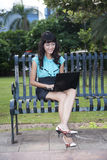 Businesswoman working outdoor. Young businesswoman working on a laptop while sitting on a bench Stock Photography