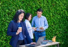 Businesswoman working outside office with team at green leaf wall,business on go and using digital technology device to corporate stock photo