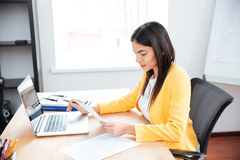 Businesswoman working with papers and laptop computer Stock Image