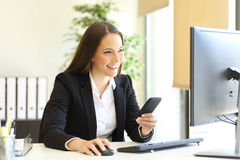 Businesswoman working with phone and computer. Happy businesswoman working checking smart phone information with a desktop computer at office Stock Photo