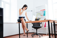 Businesswoman working with phone and laptop computer in office Stock Images