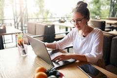 Businesswoman working remotely at cafe with headset and laptop. Mixed race female performing business negotiations on stock photography