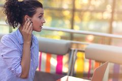 Mixed race female performing business negotiations on video chat. Telecommuting concept. Businesswoman working remotely at cafe with headset and laptop. Mixed royalty free stock photography