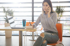 Businesswoman working remotely talking on mobile Stock Image