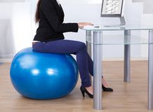 Businesswoman working while sitting on pilates ball Royalty Free Stock Photo