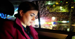 Businesswoman working while travelling in car stock video footage