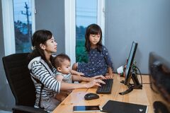 Businesswoman Working While Taking Care Children Royalty Free Stock Photos