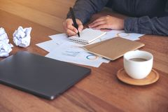 A businesswoman working and writing down on a white blank notebook with screwed up papers. Closeup image of a businesswoman working and writing down on a white stock image