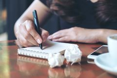 A businesswoman working and writing down on a white blank notebook with screwed up papers on table. Closeup image of a businesswoman working and writing down on Stock Images