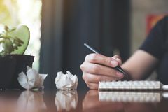 A businesswoman working and writing down on a white blank notebook with screwed up papers on table. Closeup image of a businesswoman working and writing down on Stock Photo