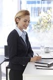 Businesswoman working. Writing notes, smiling Stock Photography