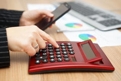 Businesswoman in workplace is calculating and dialing on mobile Royalty Free Stock Photo
