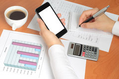 Businesswoman works at her workplace. With smartphone, graphs and tables stock image