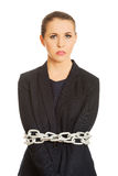 Businesswoman wrapped with metal chain. Royalty Free Stock Photo