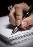 Businesswoman write something. Hand of a young business woman working with documents. Workplace of business people Stock Image