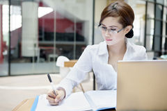 Businesswoman writes on a document Stock Image