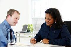 Businesswoman Writing. Businesswoman in her office with co-worker Royalty Free Stock Image