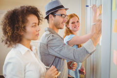 Businesswoman writing on adhesive notes on glass wall with colleagues Stock Photography