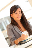Businesswoman writing on agenda Royalty Free Stock Images