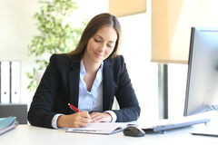 Businesswoman writing in an agenda at office Royalty Free Stock Images