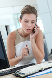 Businesswoman writing in agenda and talking on the phone Stock Image