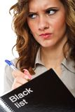 Businesswoman writing a black list. Angry businesswoman writing names in a black list notebook Royalty Free Stock Images
